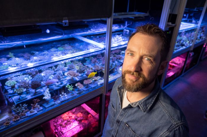 Jamie Craggs stands in front of the aquarium in which he grows coral